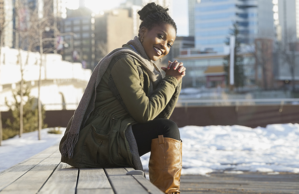 Dark-skinned woman wearing stylish winter clothes and knee-high boots
