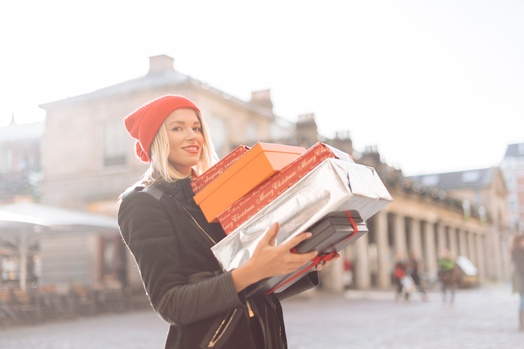 woman in winter clothes carrying presents