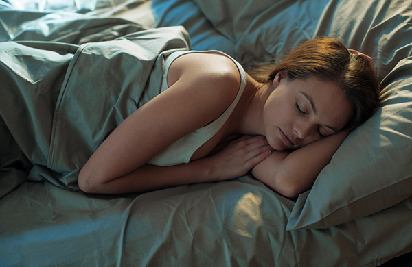 Woman sleeping in bed with grey bed sheets