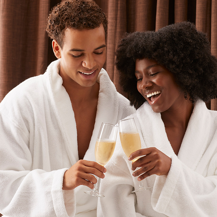 couple in robes clinking champagne flutes at the spa