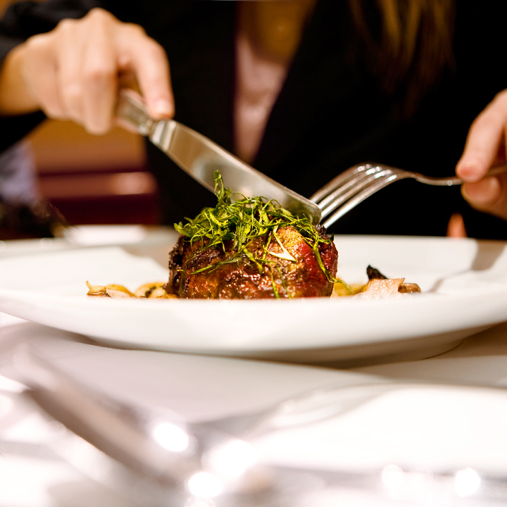 woman cutting into filet mignon steak